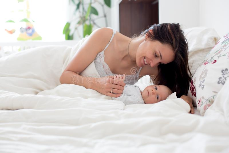 Young mother sleeping with her baby, holding him in her arms and. Smiling from happiness stock photo