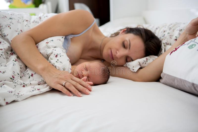 Young mother sleeping with her baby, holding him. In her arms and smiling from happiness royalty free stock photography