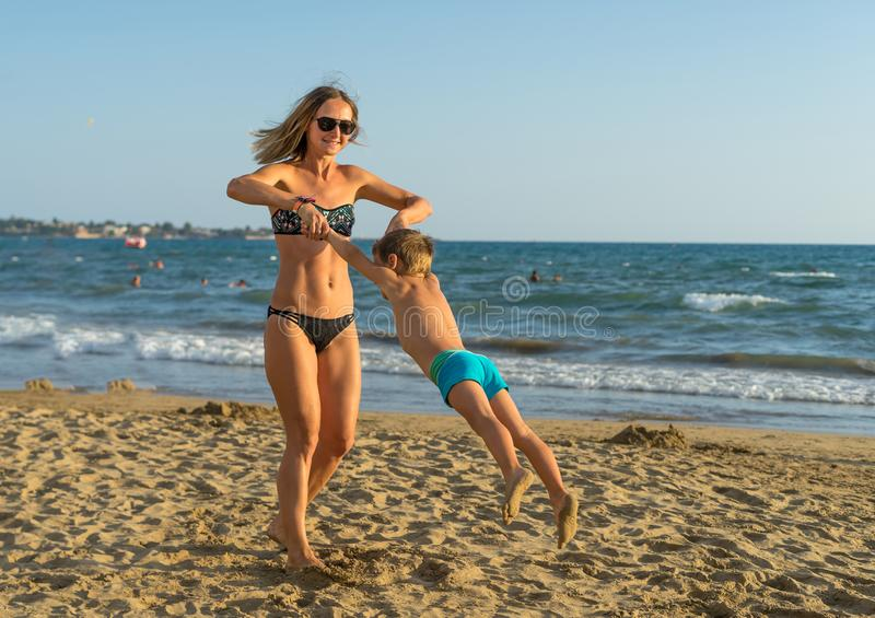 Young mother and smiling baby boy son playing on the beach in the day time. Positive human emotions, feelings, joy. Funny cute chi royalty free stock images