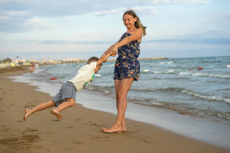 Young mother and smiling baby boy son playing on the beach on the Sunset. Positive human emotions, feelings, joy. Funny cute child. Making vacations and stock images