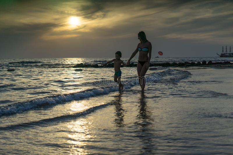 Young mother and smiling baby boy son playing on the beach on the Sunset. Positive human emotions, feelings, joy. Funny cute child. Making vacations and royalty free stock photos