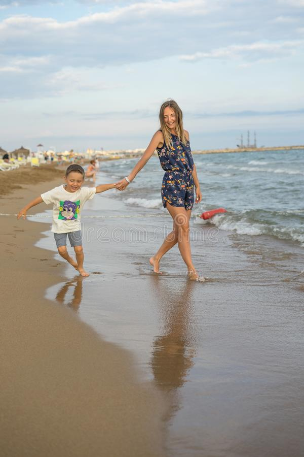 Young mother and smiling baby boy son playing on the beach on the Sunset. Positive human emotions, feelings, joy. Funny cute child. Making vacations and stock image