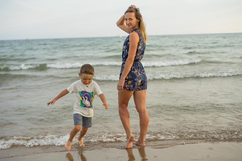 Young mother and smiling baby boy son playing on the beach on the Sunset. Positive human emotions, feelings, joy. Funny cute child. Making vacations and stock photo
