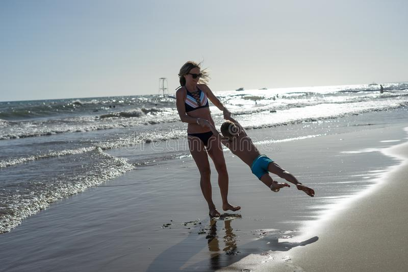 Young mother and smiling baby boy son playing on the beach on the Sunset. Positive human emotions, feelings, joy. Funny cute child stock image