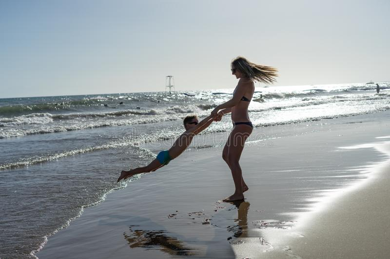 Young mother and smiling baby boy son playing on the beach on the Sunset. Positive human emotions, feelings, joy. Funny cute child stock photos