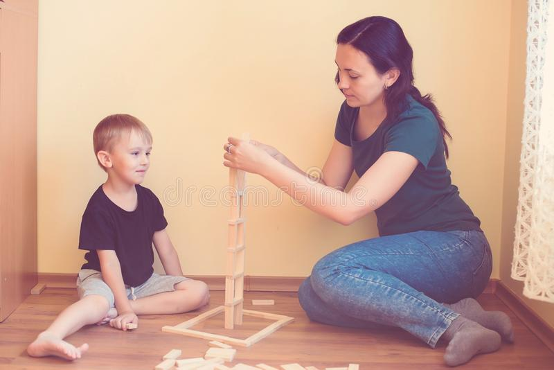 Young mother and son playing with wooden blocks indoor. Happy family spends time together at home. stock photography