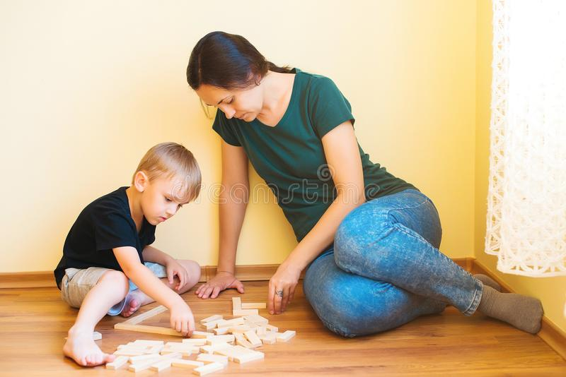 Young mother and son playing with wooden blocks indoor. Happy family spends time together at home. stock photo