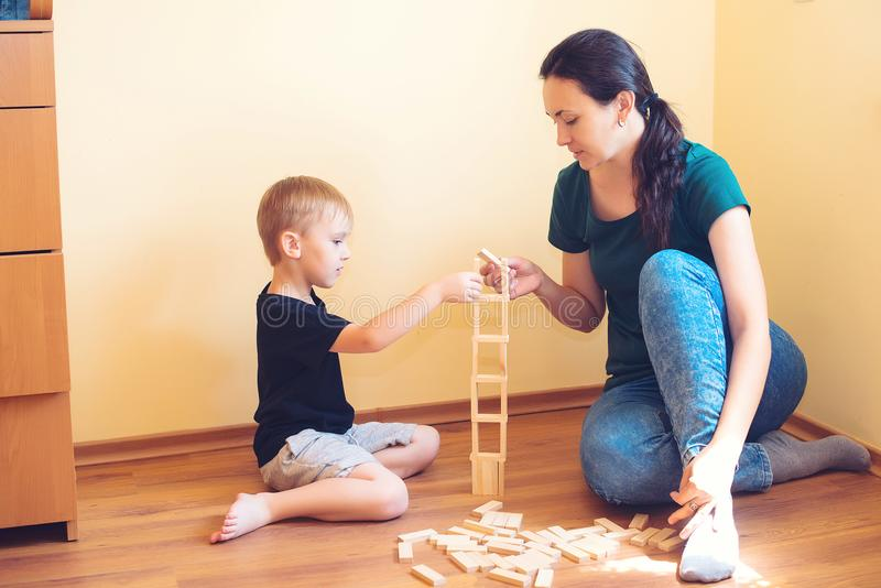 Young mother and son playing with wooden blocks indoor. Happy family spends time together at home. stock images