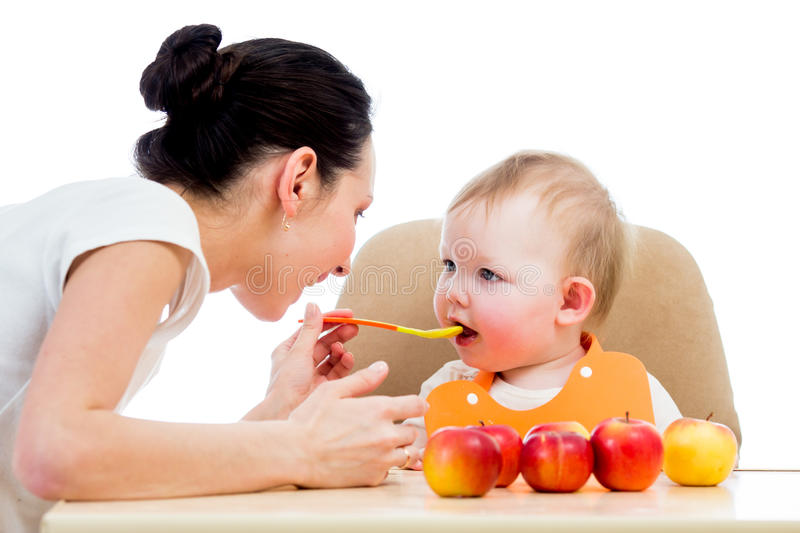 Young mother spoon-feeding her baby girl stock photo