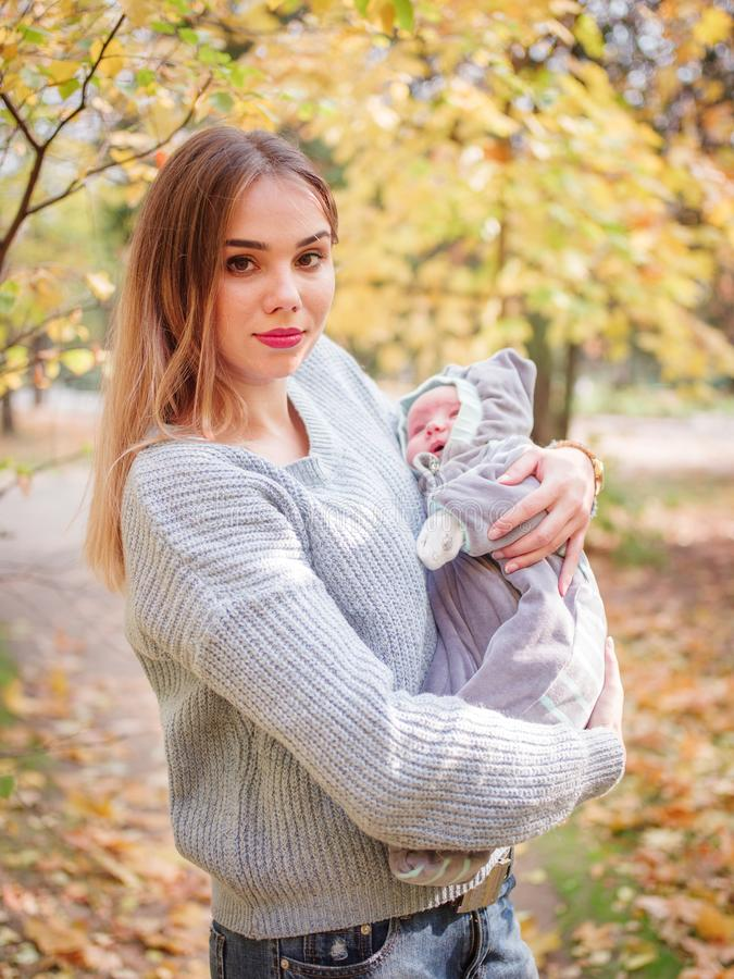 A young mother, stands in an autumn park and holds a cute baby. The concept of a happy family. royalty free stock photos