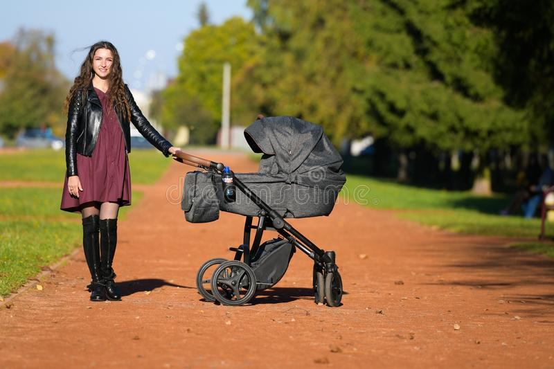 Young mother with a stroller. family, child and parenthood concept - happy mother walks with a stroller in the park stock photo