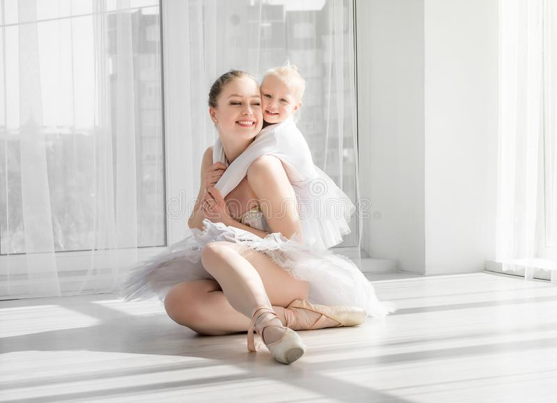 Young mother hugging little smiling daughter in ballet studio stock photo