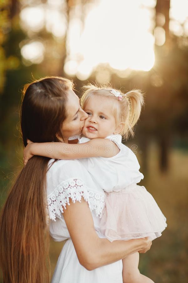 Young mother taking care of her little baby girl. mom and her daughter outdoors. Loving family. Mother`s day concept stock photo