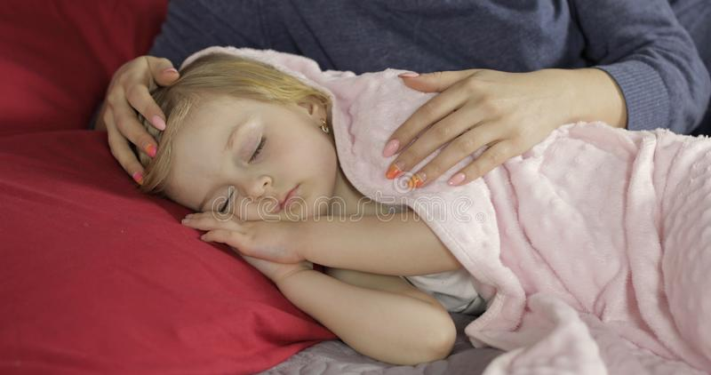 Cute baby sleeping on the bed at home. Little girl sleeping in morning light royalty free stock photo