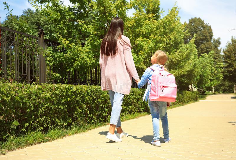 Mother taking her little child to school through park. Young mother taking her little child to school through park stock photo