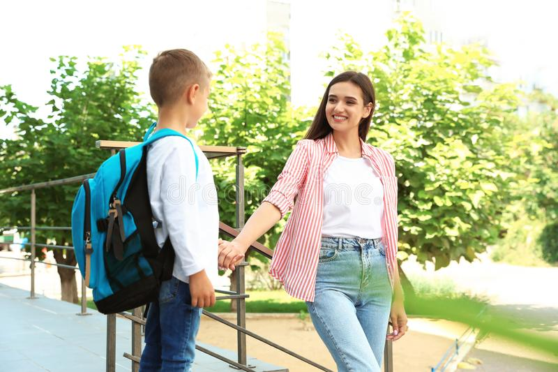 Young mother taking her little child to school. Outdoors royalty free stock photo
