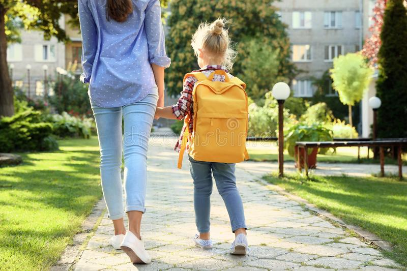Young mother taking her little child to school royalty free stock photography