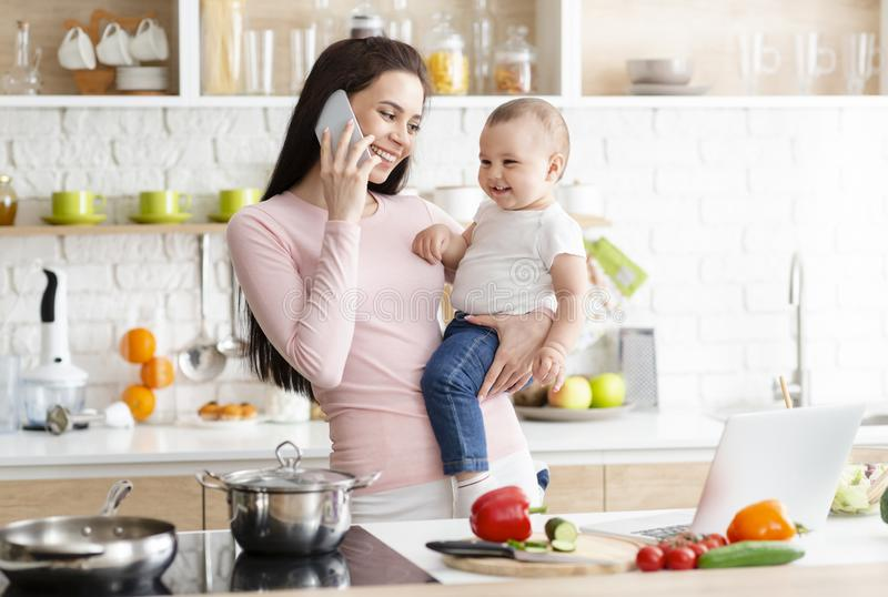 Young mother talking on phone, holding her baby at kitchen stock photo