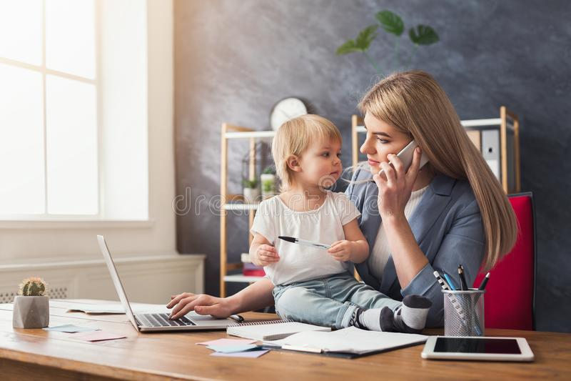 Young mother talking on phone and spending time with baby stock photos