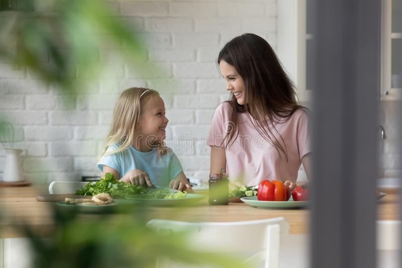 Mother share family recipes teaches daughter preparing vegetable salad royalty free stock images
