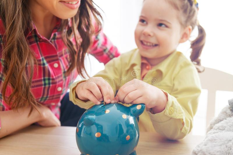 Young mother teaches her daughter to save money. stock photography
