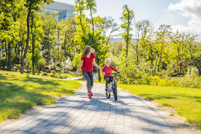 Young mother teaching her son how to ride a bicycle in the park royalty free stock photo