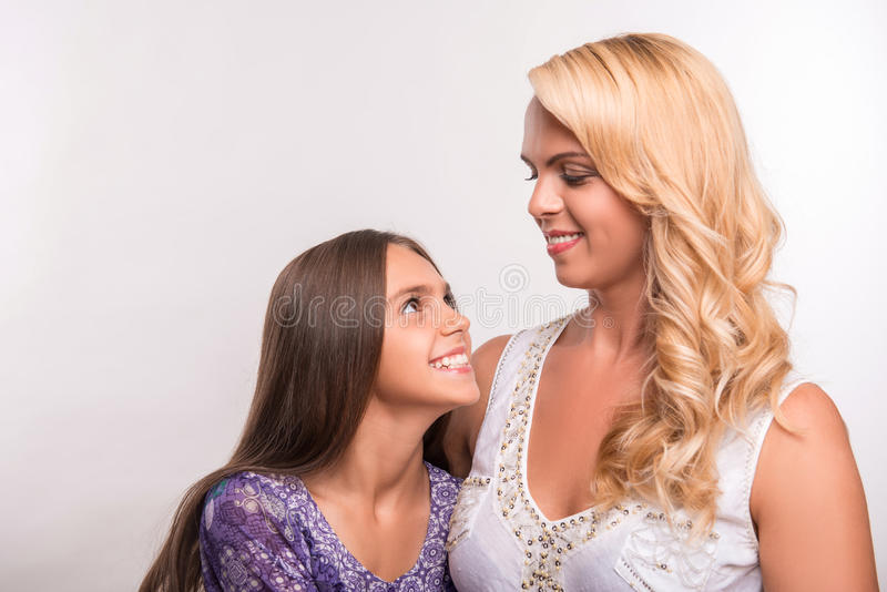 Young mother and teenager daughter. Young mother embracing daughter teenager looking at each other isolated on white background with copy place royalty free stock photography