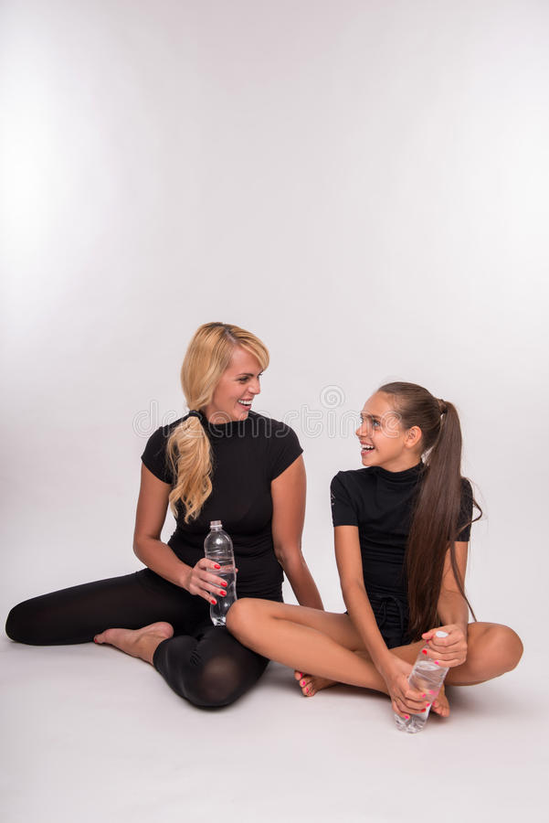 Young mother and teenager daughter. Young sport mother with bottle of mineral water and her daughter teenager sitting on floor smiling looking at each other stock photos