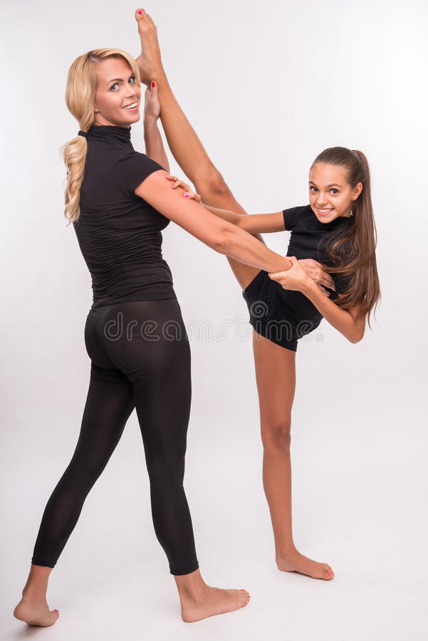 Young mother and teenager daughter. Young sport mother and her daughter teenager doing splits looking at camera isolated on white background with copy place royalty free stock photos