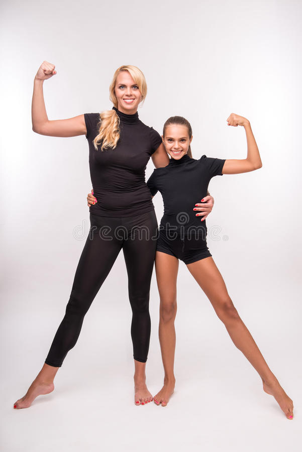 Young mother and teenager daughter. Young sport mother and her daughter teenager showing their muscles looking at camera isolated on white background stock photos