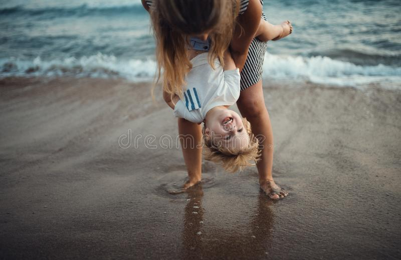 Young mother with a toddler boy standing on beach on summer holiday, having fun. stock photos