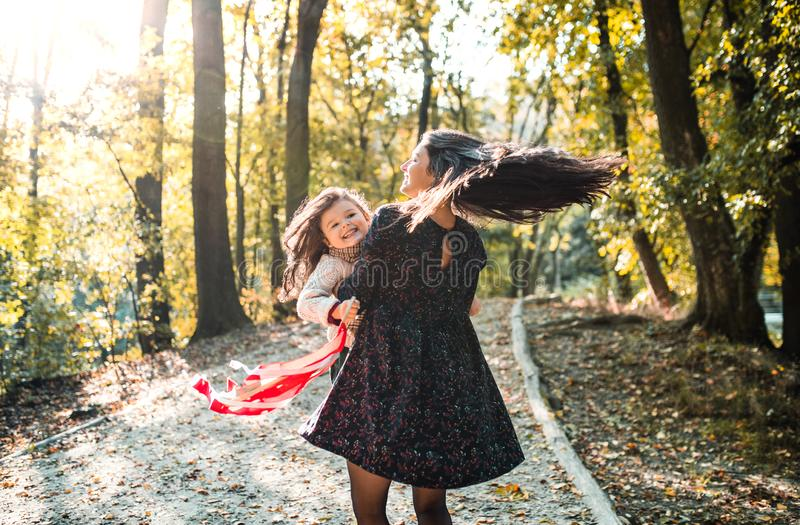 A young mother with a toddler daughter in forest in autumn nature, having fun. stock images