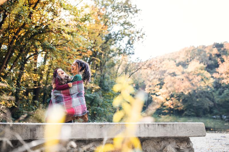A young mother with a toddler daughter having fun in forest in autumn nature. royalty free stock photography