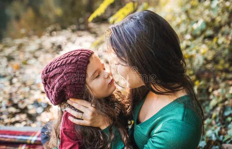 A young mother with a toddler daughter hugging and kissing in forest in autumn nature. stock photography