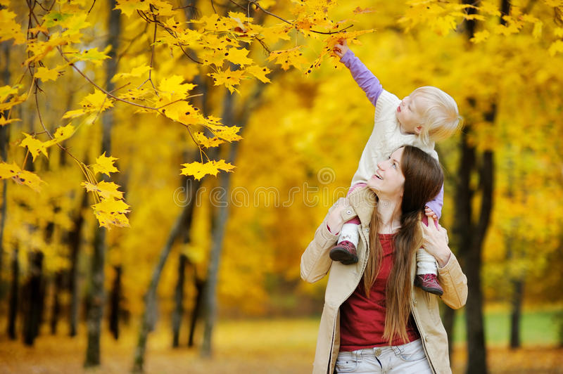 Young mother and toddler girl have fun at autumn royalty free stock image