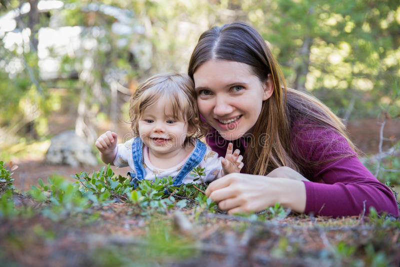 Young mother and toddler girl lying on the ground royalty free stock photos