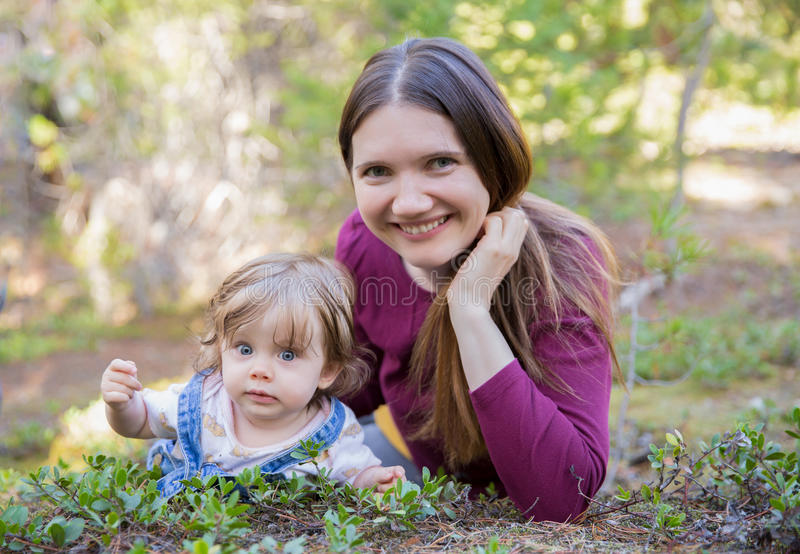 Young mother and toddler girl lying on the ground royalty free stock photography