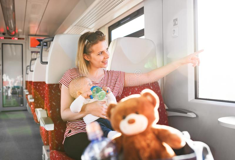 Young mother travelling with baby by train. royalty free stock photography