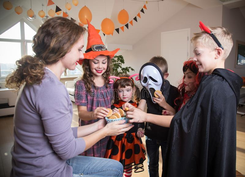 Kids in Halloween party. Young mother treats children with sweets and halloween royalty free stock images