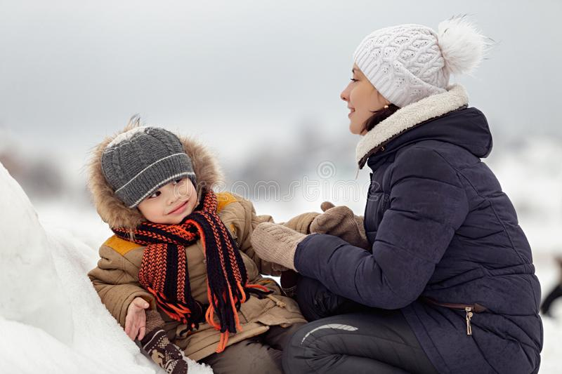 Young mother and little son sitting on spring snow stock photo