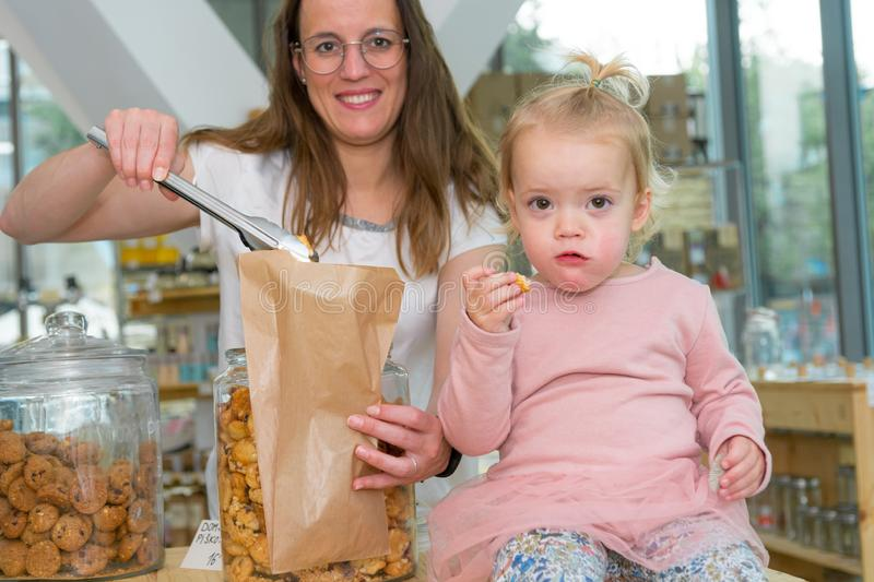 Young mother trying to fill bag with delicious cookies while her mother is eating them. stock image