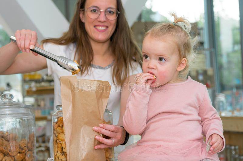 Young mother trying to fill bag with delicious cookies while her mother is eating them. stock images