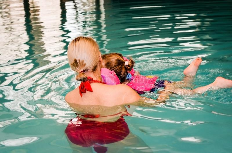 Young  mother trying to learn to swim on her little daughter in the indoor  pool . Vintage filter stock images
