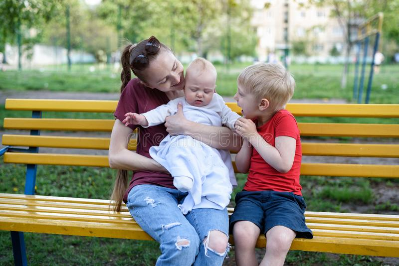 Young mother and two children on a bench in the park. Baby and blond elder brother playing. Spring warm day stock image