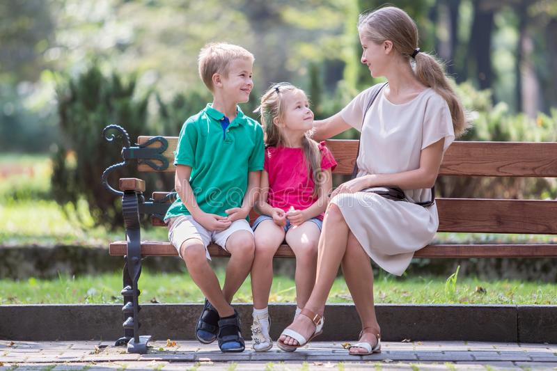 Young mother and two children boy and girl having fun time together on a bench in summer park stock photo