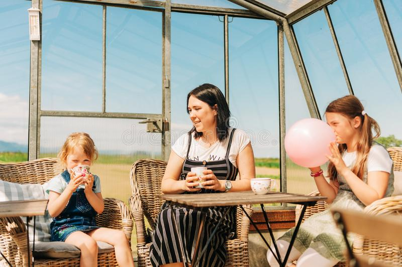 Young mother with two daughters enjoying sunny day stock photo