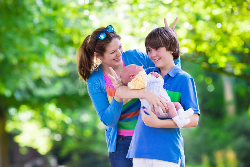 Young mother with two kids in a park. Mother and children play in a park. Young mom with two sons, newborn and teenager boy. Siblings with big age difference royalty free stock images