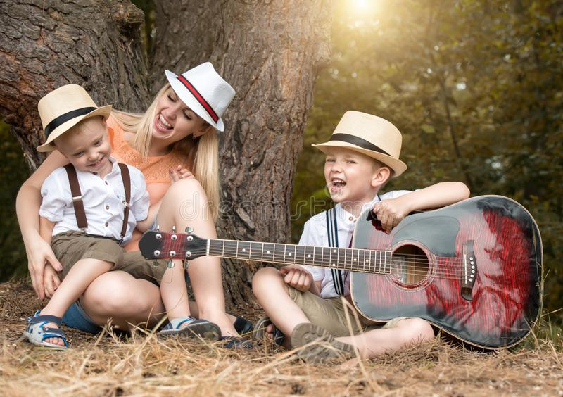 Young mother and two sons are resting in the woods,singing songs with a guitar. stock images
