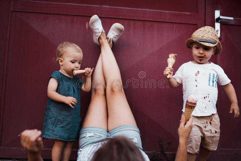 A young mother with two toddler children outdoors in summer, eating ice cream. stock photos