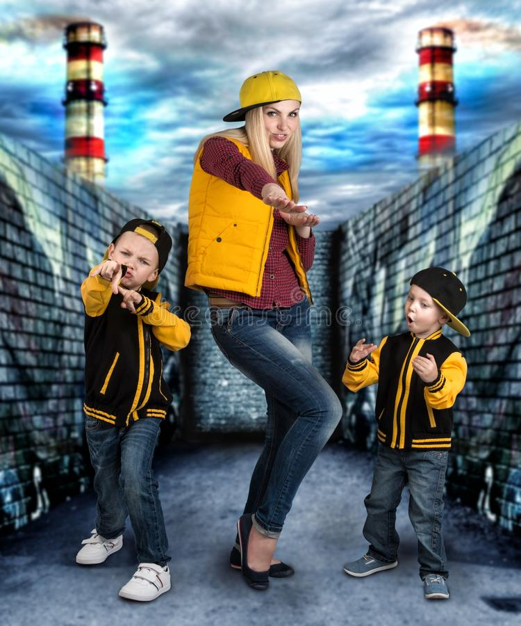 A young mother and two young sons in the style of hip hop.Fashionable family.Graffiti on the walls. royalty free stock images